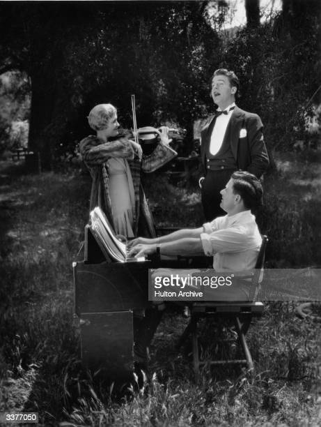 Laura La Plante plays the violin accompanied by costar Neil Hamilton on the piano while director William Wyler sings during a break in filming 'The...