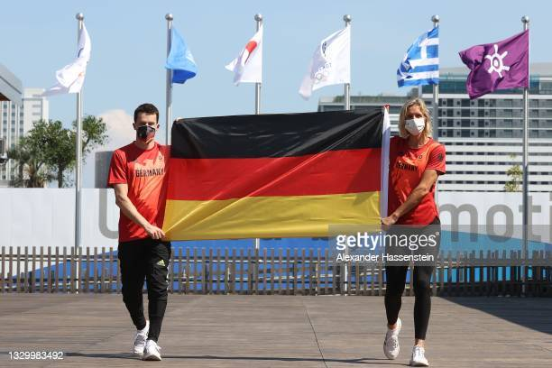 Laura Ludwig and Patrick Hausding of Team Germany pose with the German flag at the Olympic Village after have been announced as flag bearers for team...