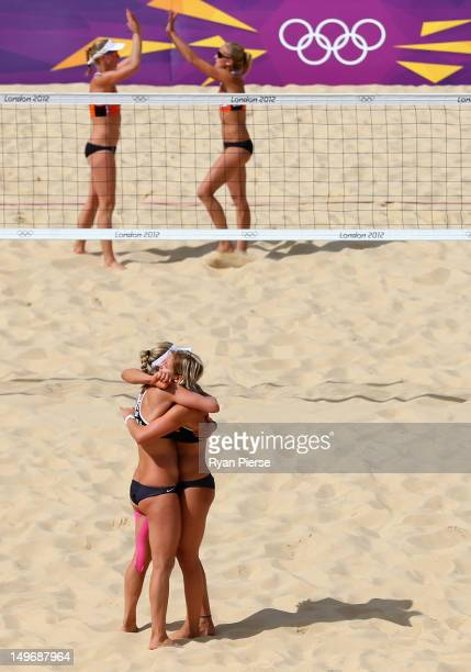Laura Ludwig and Sara Goller of Germany celebrate after winning match point during the Women's Beach Volleyball preliminary match between Germany and...