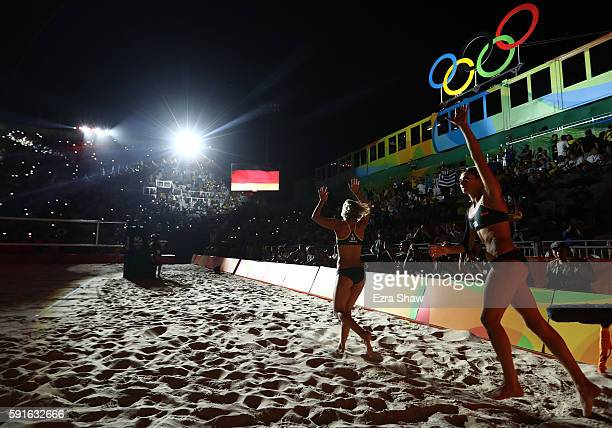 Laura Ludwig of Germany and Kira Walkenhorst of Germany wave to the crowd before the Beach Volleyball Women's Gold medal match against Agatha...