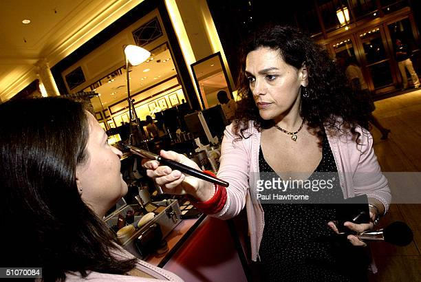 Laura Mercier applies makeup at her cosmetic counter as she attends the Brushes With Greatness makeup artist event at Saks Fifth Avenue July 14 2004...