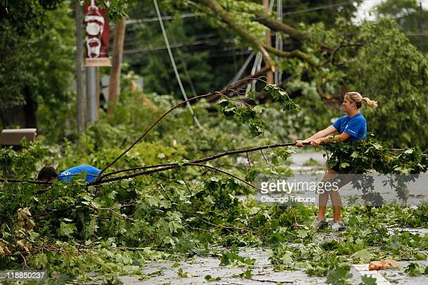 Laura Micksch right helps Nick Dowman remove debris Monday July 11 2011 in Gurnee Illinois after a morning windstorm downed trees and caused power...