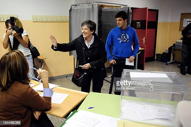 Laura Mintegi candidate of proindependence Basque political parties coalition Euskal Herria Bildu gestures next to her son after casting her ballot...