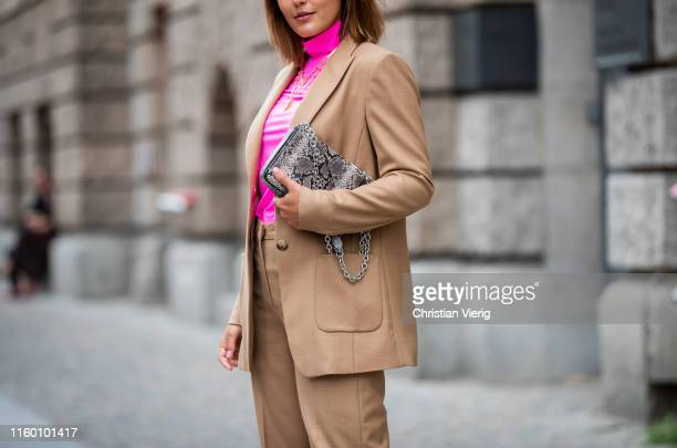 Laura Noltemeyer is seen wearing total look Marc Cain brown suit pink turtleneck bag with snake print during Berlin Fashion Week on July 02 2019 in...