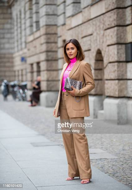 Laura Noltemeyer is seen wearing total look Marc Cain brown suit, pink turtleneck, bag with snake print during Berlin Fashion Week on July 02, 2019...