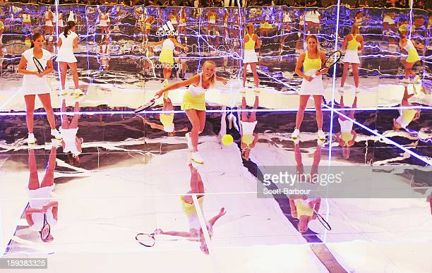 Laura Robson of Great Britain and Maria Kirilenko of Russia watch as Caroline Wozniacki of Denmark plays a shot on a mirror court at the Adidas by...