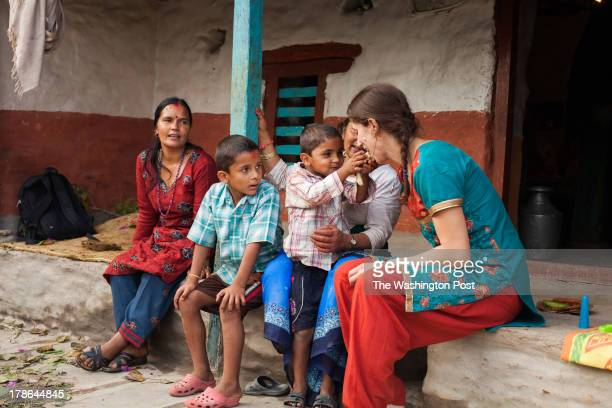 Laura Spero visits with her Nepali nephews Aidan and Pascal Dahal at Radhika Subedi's house while their mother Malika Subedi looks on