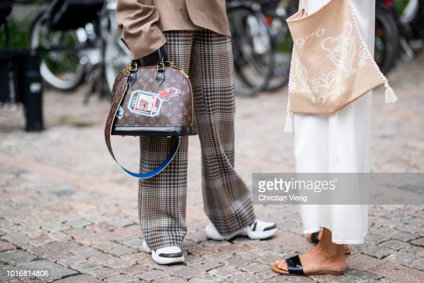 Laura Tonder wearing brown jacket with belt and long oversized sleves checked pants Louis Vuitton bag and sneakers and Celine Aagaard wearing sandals...