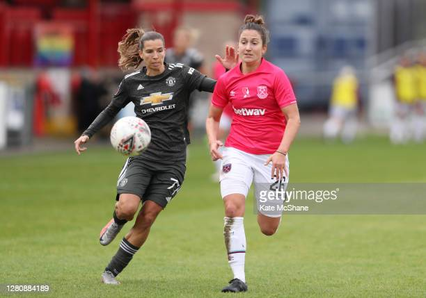 Laura Vetterlein of West Ham United is challenged by Tobin Heath of Manchester United during the Barclays FA Women's Super League match between West...