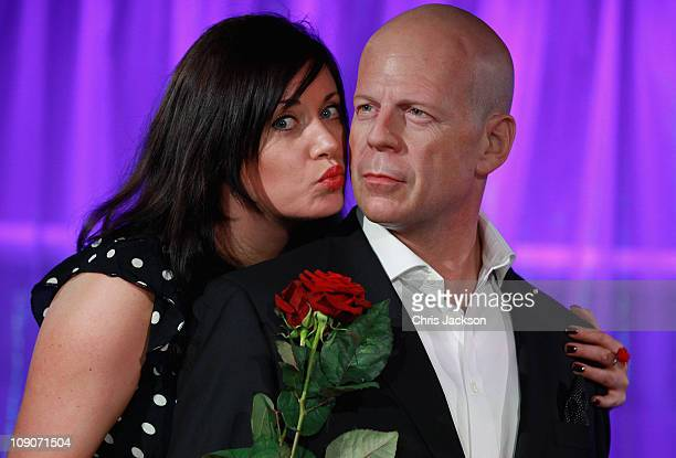 Laura Watson kisses a waxwork model of Bruce Willis at Madame Tussauds on February 14 2011 in London England The waxwork of the actor has been...