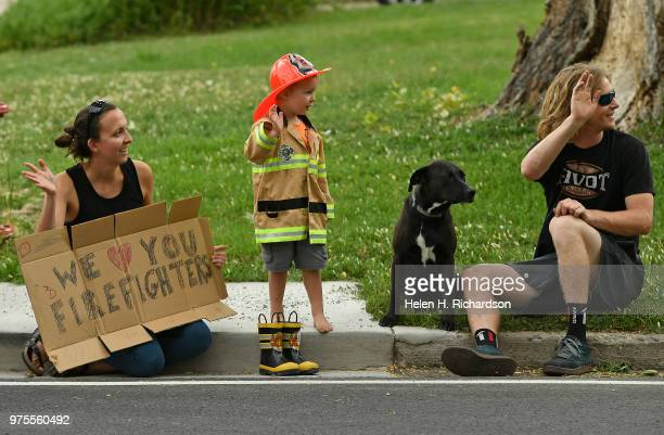 Laura Wegner left and her husband Patrick right with their dog Windy brought their son Silas out in his firefighter costume to wave to firefighters...