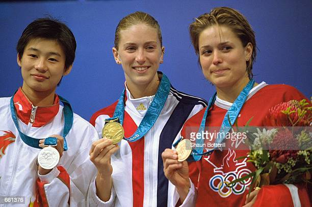 Laura Wilkinson of the United States center shows off her Gold Medal as Li Na of China left displays her Silver and Anne Montminy of Canada holds her...