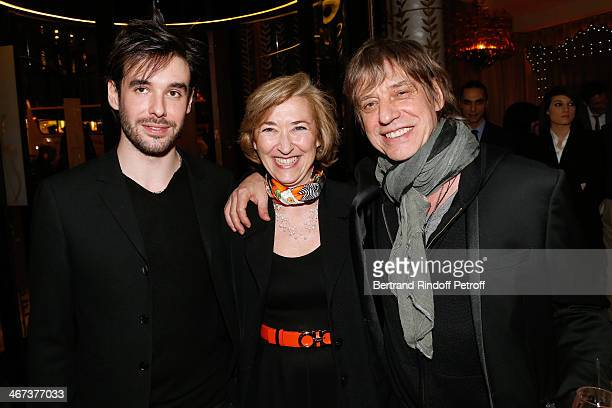 Laure Du Manoir standing between Singer JeanLouis Aubert his son Arthur Aubert attend the Arthur Aubert Exhibition private view Held at Le Fouquet's...