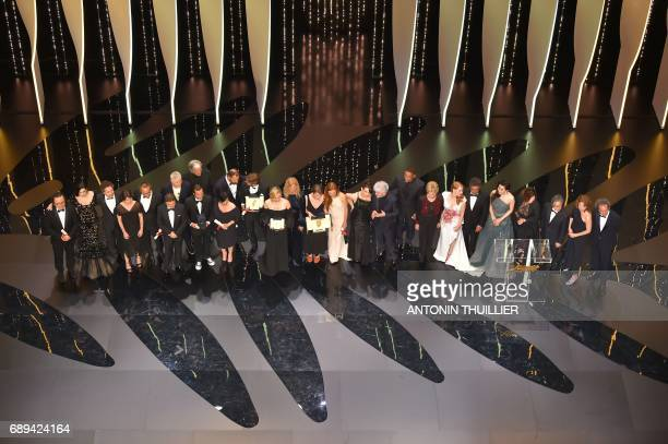 Laureates and jury members stand on stage around Swedish director Ruben Ostlund after he won the Palme d'Or for his film 'The Square' on May 28 2017...
