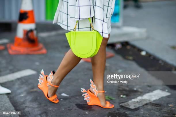 Laureen Uy wearing white checked jacket orange Prada heels Wandler neon bag is seen outside Ingie Paris during Paris Fashion Week Womenswear...