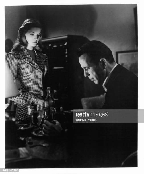 Lauren Bacall looking down at Humphrey Bogart as he drinks in a scene from the film 'To Have And Have Not' 1944