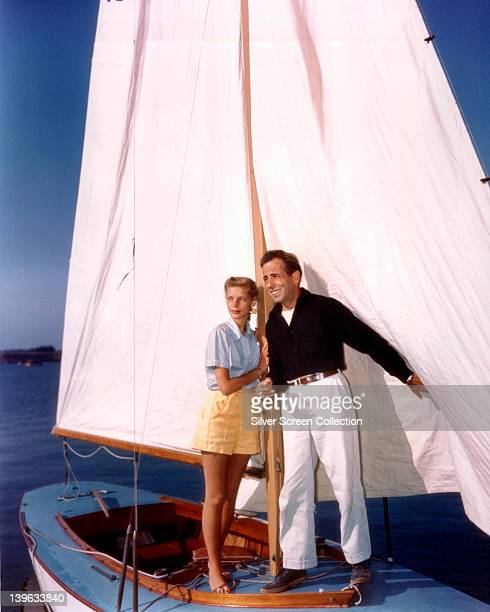 Lauren Bacall US actress and her husband Humphrey Bogart US actor support themselves by holding the mast on a small sailboat circa 1950