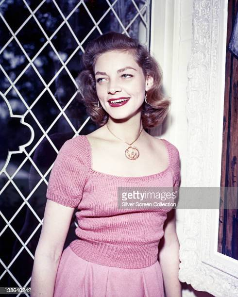 Lauren Bacall US actress wearing a pink short sleeve jumper and a pink skirt smiling as she poses beside a window circa 1955