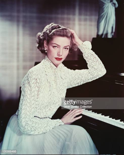 Lauren Bacall, US actress, wearing a white macrame blouse and a light blue skirt while posing beside a piano, with one hand on the keys, circa 1955.