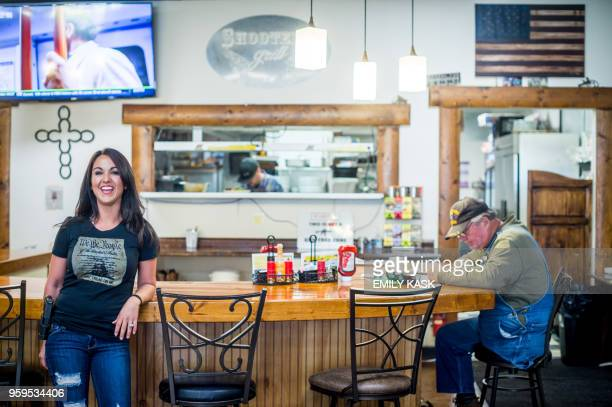 Lauren Boebert stands by the counter with a dining customer inside Shooters Grill in Rifle, Colorado on April 24, 2018. - Lauren Boebert opened...