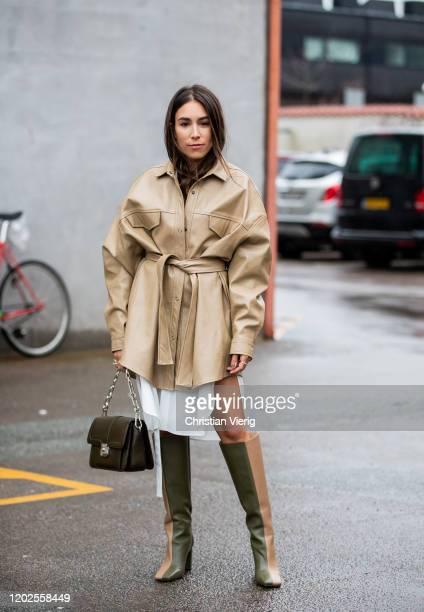 Lauren Caruso wearing beige belted jacket, twon tone boot, green bag, dress seen outside Carcel on Day 1 during Copenhagen Fashion Week Autumn/Winter...