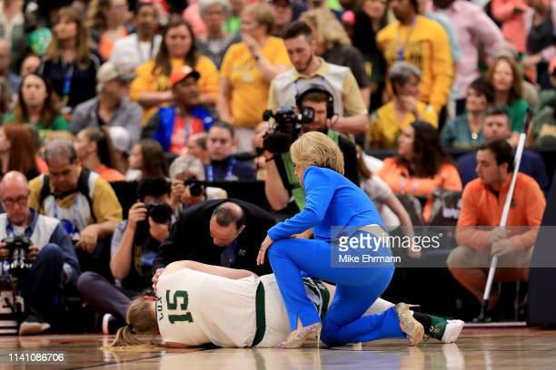 Lauren Cox of the Baylor Lady Bears is tended to by the trainer and head coach Kim Mulkey after sustaining a leg injury during the third quarter in...