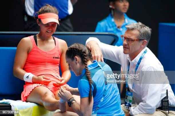 Lauren Davis of the United States receives medical treatment after injuring her foot in a fall in her third round match against Simona Halep of...