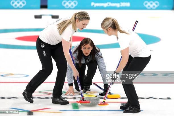 Lauren Gray left and Vicki Adams sweep the ice in front of a stone cast by Eve Muirhead of Great Britain during Women's Round Robin Session 1 on day...
