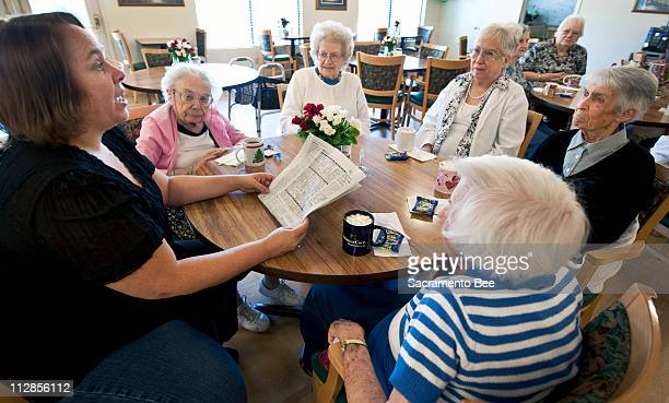 Lauren Guarducci left reads the Dear Abby column to seniors at the Almond Avenue Residence Club in Orangevale California on July 22 2010 The group...