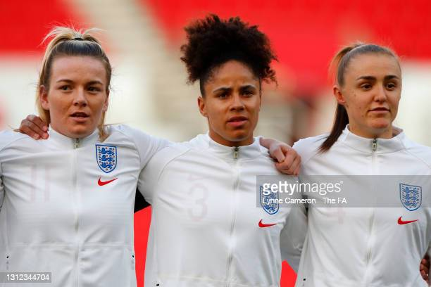 Lauren Hemp, Demi Stokes and Georgia Stanway of England stand for the national anthem prior to the International Friendly match between England and...