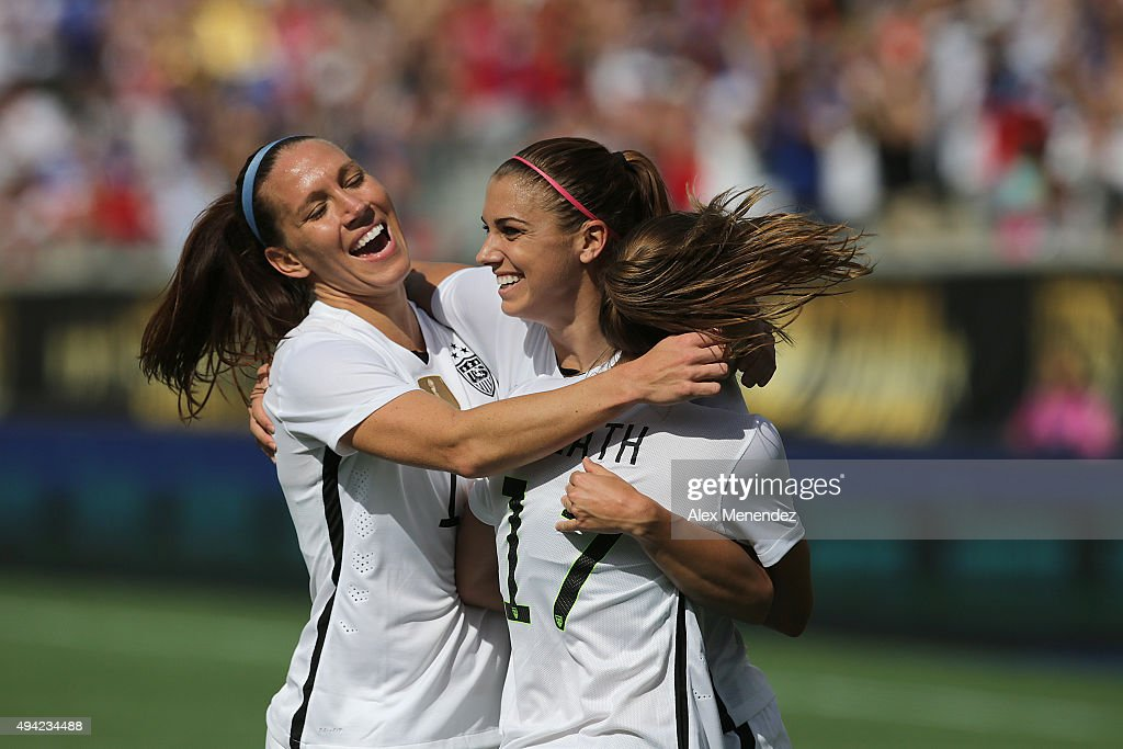 Lauren Holiday #12, Alex Morgan #13, and Tobin Heath #17 of USWNT celebrate a goal during a women's international friendly soccer match between Brazil and the United States at the Orlando Citrus Bowl on October 25, 2015 in Orlando, Florida.