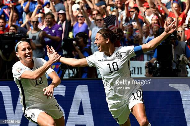 Lauren Holiday and Carli Lloyd of the United States celebrate with teammates after Lloyd scores her second goal against Japan in the FIFA Women's...