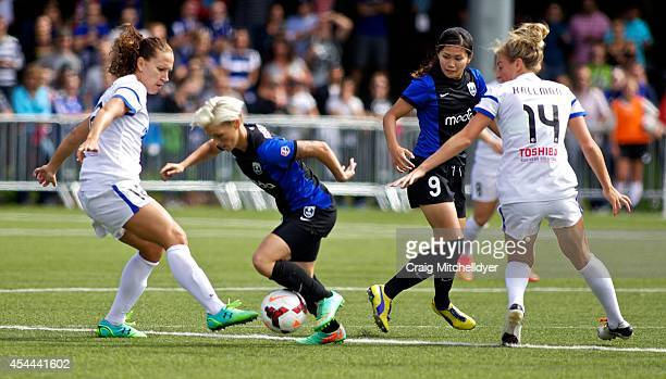 Lauren Holiday of FC Kansas City kicks the ball away from Jessica Fishlock of Seattle Reign FC in the first half of the National Women's Soccer...