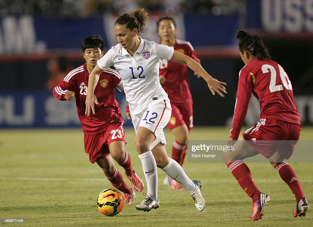 Lauren Holiday #12 of the United States dribbles the ball in the first half of the game away from Li Dongna #26 and Ren Guixin #23 of China during an international firendly match at Qualcomm Stadium on April 10, 2014 in San Diego, California.
