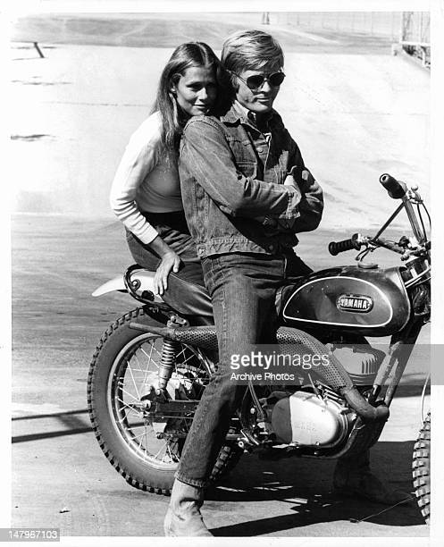 Lauren Hutton sitting on motor bike with Robert Redford in a scene from the film 'Little Fauss And Big Halsy' 1970