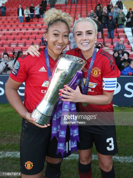 Lauren James and Alex Greenwood of Manchester United Women pose with the FA Women's Championship trophy after the WSL match between Manchester United...