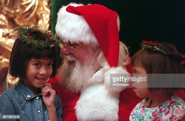 MESA––Lauren left and Lindsay Forbes of La Mirada contemplate their Christmas desires with Santa Claus at South Coast Plaza in Costa Mesa Friday