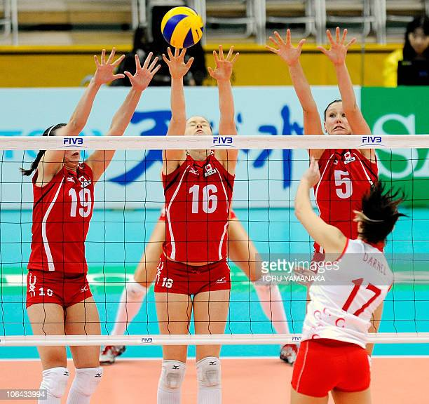 Lauren O'Reilly Jennifer Hinze and Tiffany Dodds of Canada try to block a spike from Neslihan Darnel of Turkey during their first round match of the...