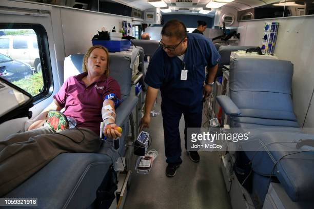 Lauren Paige gives blood while phlebotomist Alfredo Lacanilao checks her progress during a blood drive at La Reina High School after a mass shooting...