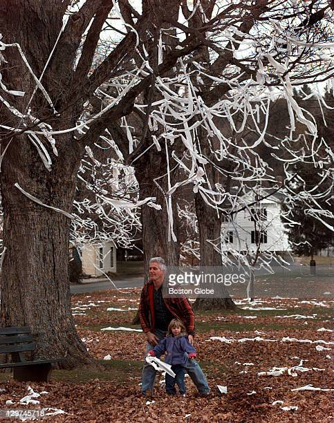 Lauren Plumley and her dad Bruce Plumley walk to their home next to the Brimfield Town Common which has trees decorated with dozens of rolls of...