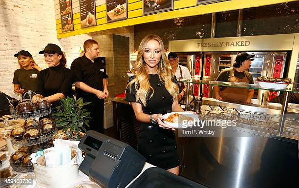 Lauren Pope from 'The Only Way Is Essex' helps serve behind the counter at the Spudulike opening at Lakeside Shopping Centre on November 22 2014 in...