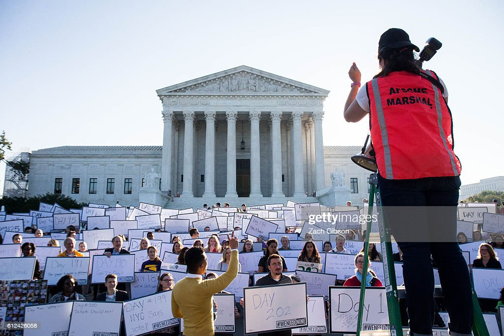 Lauren Santa Cruz organizes demonstrators for a group photo during a demonstration urging the U.S. Senate to hold a confirmation vote for Supreme Court Nominee Merrick Garland outside of The Supreme Court of the United States on October 4, 2016 in Washington, DC. Today marks the 202nd day since President Barack Obama nominated Judge Garland to fill the vacancy left after former Justice Antonin Scalia passed away in February.
