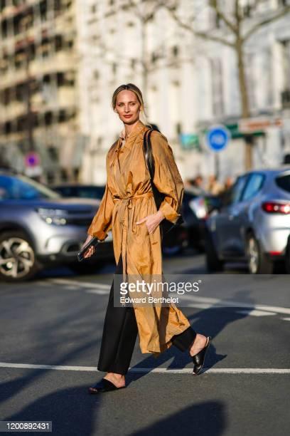 Lauren Santo Domingo wears a camel flowing long trench coat, a black bag, black pants, black flat mules, outside Dior, during Paris Fashion Week -...