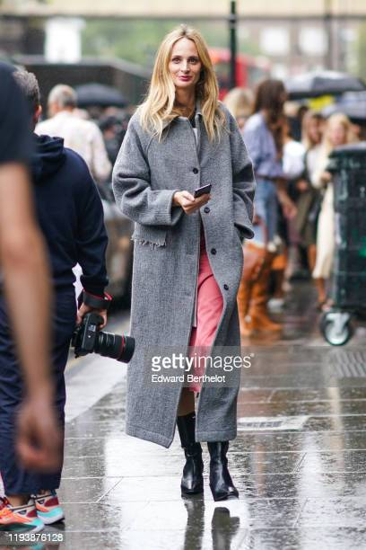Lauren Santo Domingo wears a gray long coat pink pants black leather boots during London Fashion Week September 2019 on September 16 2019 in London...