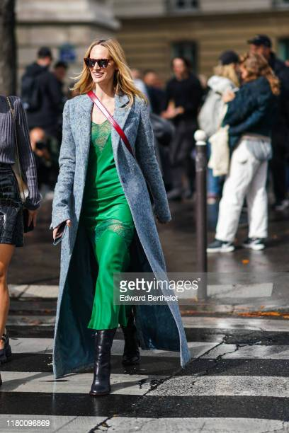 Lauren Santo Domingo wears sunglasses, a long light blue wool coat, a green dress with a green lace yoke and a green lace insert a the thighs, black...