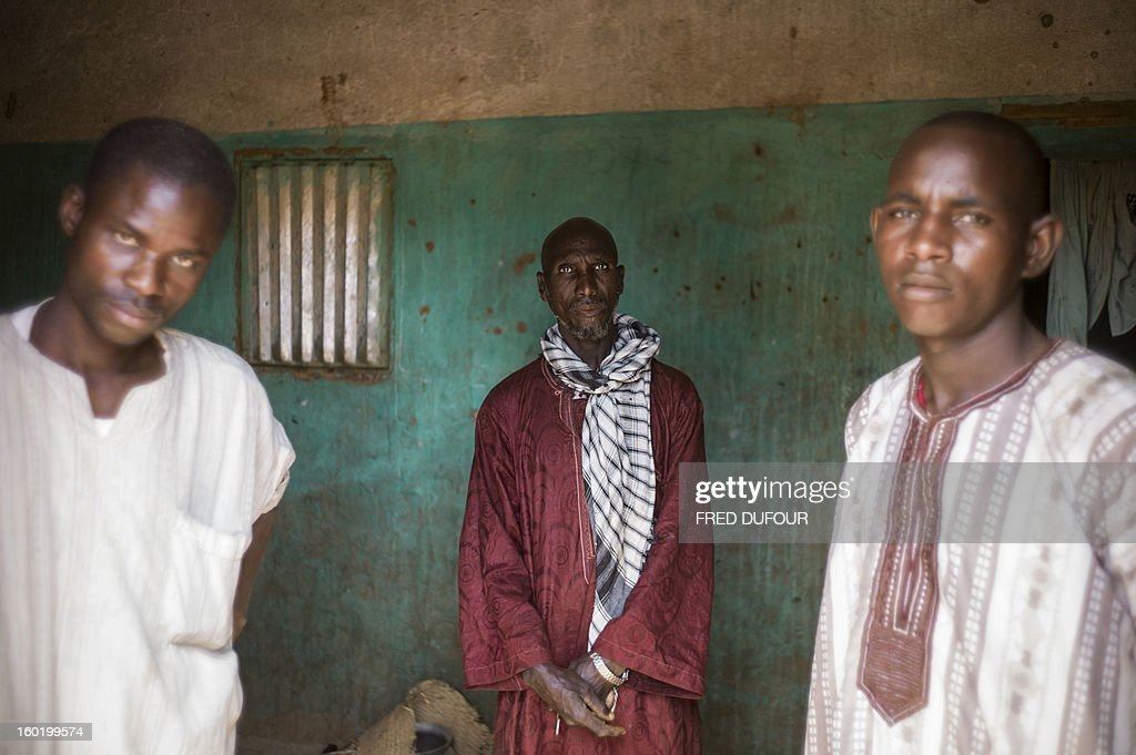 Laurence BOUTREUX - Idrissa Maiga (C), a Malian farmer, poses with two of his sons in his house in Konna on January 27, 2013. Maiga's second wife, 41, and two boys and a girl aged from 10 to 14 reportedly perished on the morning of the 11 January during a French army air raid and were buried the same afternoon.