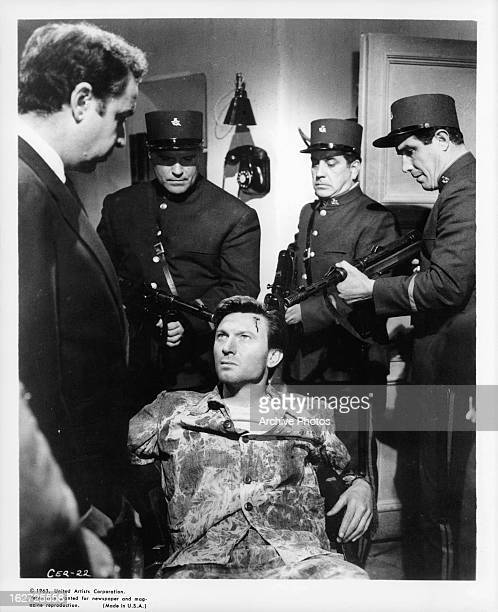 Laurence Harvey is threatened with death by a firing squad in a scene from the film 'The Ceremony' 1963
