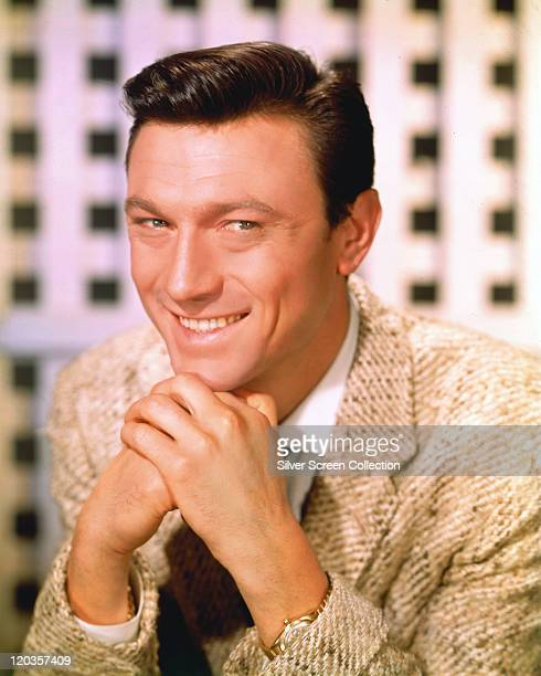Laurence Harvey Lithuanianborn actor sits smiling with his chin resting on his hands which are clasped together in front of him circa 1965