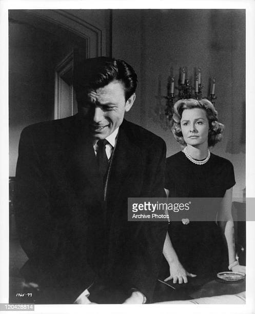Laurence Harvey on the verge of tears in front of Dina Merrill standing with guns in a scene from the film 'Butterfield 8', 1960.
