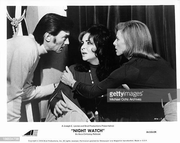 Laurence Harvey speaks to Elizabeth Taylor as she is consoled by Billie Whitelaw in a scene from the film 'Night Watch', 1973.